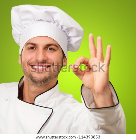 Chef Showing Ok Sign On Green Background - stock photo