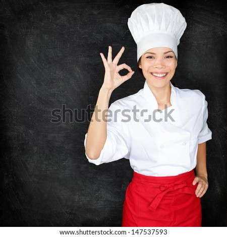 Chef showing Perfect hand sign and menu blackboard. Woman in front of blank menu blackboard. Happy female chef, cook or baker by empty chalkboard menu display wearing chef whites uniform and hat - stock photo