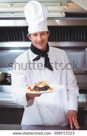 Chef showing plate of spaghetti in commercial kitchen - stock photo