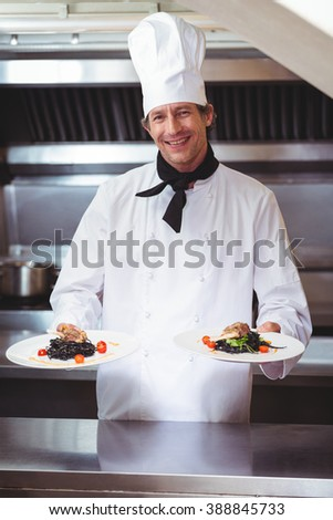 Chef showing plates of spaghetti in commercial kitchen - stock photo