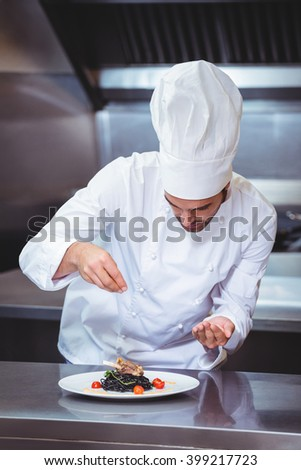 Chef sprinkling spices on dish in commercial kitchen - stock photo