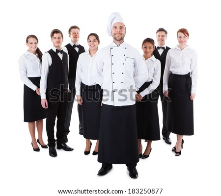 Chef standing in front of his team. Isolated on white - stock photo