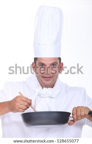 Chef stirring pan - stock photo