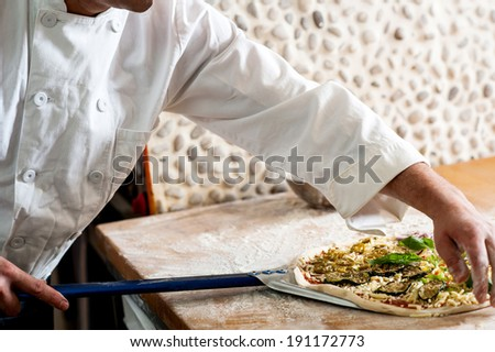 Chef taking out freshly baked pizza - stock photo