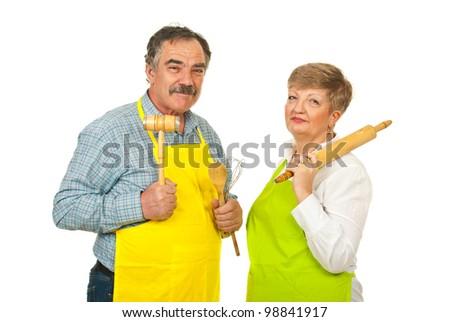 Chef team of senior couple holding kitchen utensils isolated on white background - stock photo