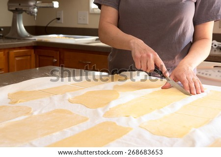 Chef trimming homemade speciality rolled pasta dough in a kitchen cutting it into sheets for making fettuccine so that it can be fed through the pasta cutting machine - stock photo