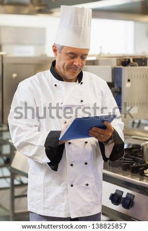 Chef using his digital tablet in the kitchen - stock photo