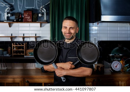 Chef with a frying pans in their hands smiling and laughing in the kitchen. Funny cook with pots. Bar, restaurant, chef, cook, concept. - stock photo