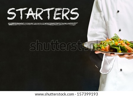 Chef with chalk starters sign written on blackboard background - stock photo