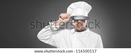 Chef with knife posing against gray background - stock photo