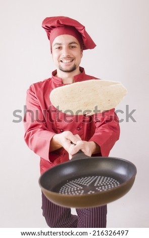 Chef with pan flips pancake in studio shot with red uniform - stock photo