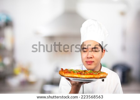 Chef with white uniform smell pizza in the kitchen - stock photo