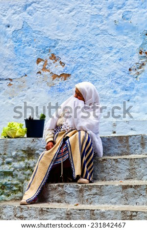 CHEFCHAOUEN, MOROCCO - JANUARY 02: An unidentified woman resting on the steps after shopping in the souk on January 02, 2014 in Chefchaouen medina, Morocco. - stock photo