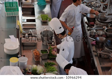 chefs at work in a restaurant - stock photo