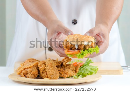 Chefs holding burger Place on a fried chicken plate for serve - stock photo