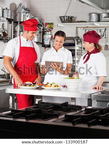 Chefs looking for recipe on a digital tablet while cooking at commercial kitchen - stock photo