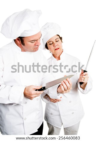 Chefs sharpening and testing the edge of their top quality knives.  Isolated on white.   - stock photo