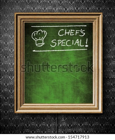 Chefs special with copy-space chalkboard in old wooden frame on vintage wall - stock photo