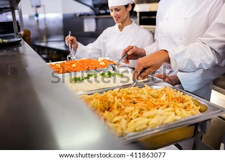 Chefs standing at serving trays of pasta in commercial kitchen - stock photo