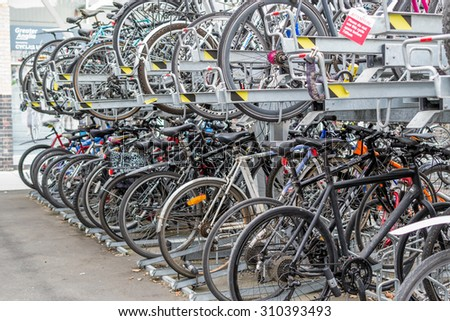 CHELMSFORD/ESSEX - ENGLAND 16TH AUGUST 2015 - Many commuter bikes parked and locked outside a train station in Chelmsford Essex in August 2015 provide ecological friendly transport for passengers - stock photo