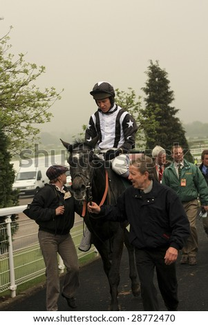 CHELTENHAM, GLOUCS, APRIL 17 2009: Jockey Richard Johnson returns muddy from competing in the second race with Quentin Collonges at the April national hunt meeting at Cheltenham Racecourse, UK - stock photo