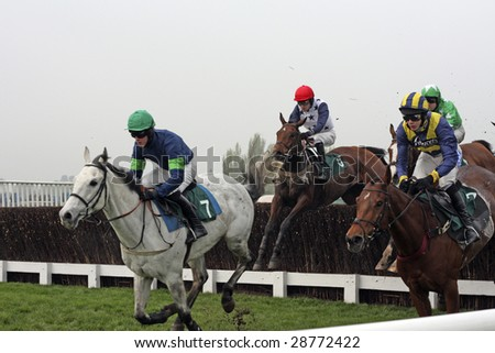 CHELTENHAM, GLOUCS, APRIL 17 2009: Tom Messenger takes the lead at the fourth fence of the April meeting at Cheltenham Racecourse national hunt meeting in Cheltenham UK - stock photo