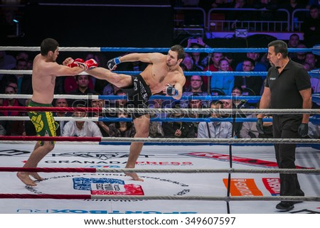 Chelyabinsk, Russia - December 5, 2015: athlete mixed martial arts fighter gets direct kick foot to his opponent. referee fight John McCarthy during Cup of Russia MMA - stock photo