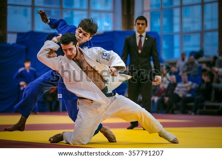 Chelyabinsk, Russia -  December 20, 2015: fight between young male judoists. in background referee during All-Russian competition on judo of memory Grigory Verichev - stock photo
