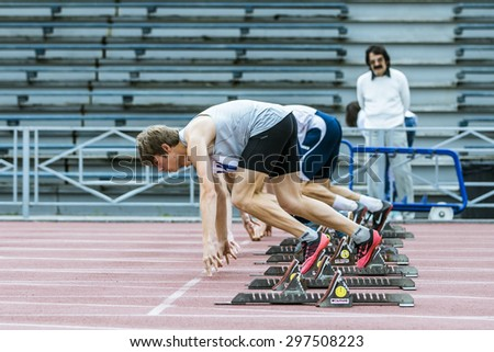 Chelyabinsk, Russia - July 10, 2015: start sprint distance of group young male athletes from starting blocks during Championship of Chelyabinsk on track and field athletics - stock photo