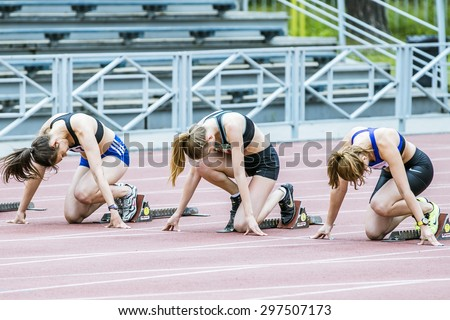 Chelyabinsk, Russia - July 10, 2015: young girls ready to start of sprint distance of 100 meters during Championship of Chelyabinsk on track and field athletics - stock photo