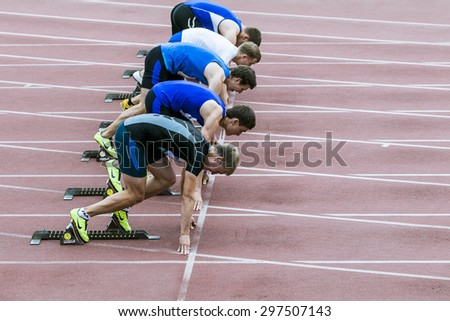 Chelyabinsk, Russia - July 10, 2015: young male athletes ready for start of sprint distance during Championship of Chelyabinsk on track and field athletics - stock photo
