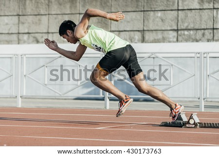Chelyabinsk, Russia - May 24, 2016: male athlete starts from starting blocks on a distance of 400 meters during UrFO Championship in athletics - stock photo