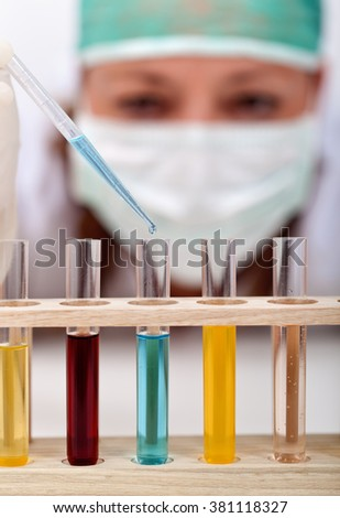 Chemical experiment in science class - woman with pipette and test-tubes, closeup - stock photo