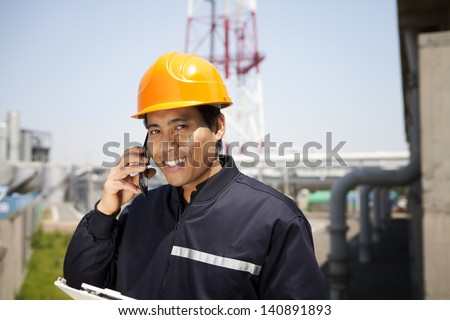 Chemical industrial engineer communication via phone looking at the camera - stock photo
