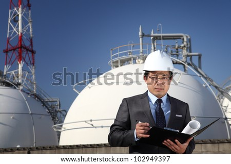 Chemical industrial engineer standing front of storage tank oil gas industry and tower writing and checking on notepad - stock photo