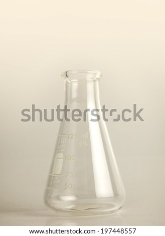 Chemical laboratory beaker, empty 125ml Erlenmeyer flask on gray background. - stock photo