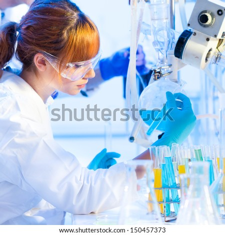 Chemical laboratory scene: attractive young PhD student and her post doctoral supervisor scientist observing the blue indicator color shift after the solution  destillation. - stock photo
