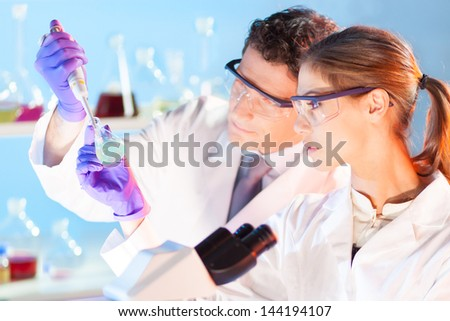 Chemical laboratory scene: attractive young student and her post doctoral supervisor scientist observing the green indicator solution color shift in glass flask. - stock photo