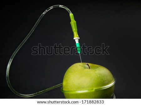 Chemical liquid in the drop counter injected into apple on a black background - stock photo