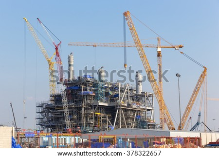 Chemical plant under construction with big crane - stock photo