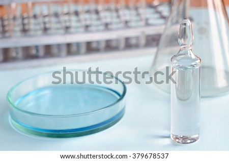 Chemical research in Petri dishes on blue background. Preparing plates in a microbiology laboratory. Inoculating plates. Vaccine ampoule. Daylight. - stock photo