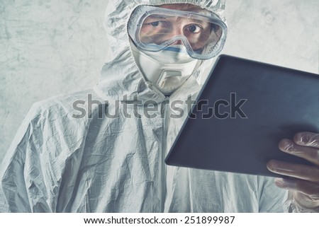 Chemical Scientist in Protective Laboratory Clothing Using Digital Tablet Computer. Selective focus with Shallow Depth of Field. - stock photo