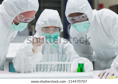 Chemist adding green liquid to test tubes with two other chemists watching in the lab - stock photo