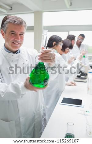 Chemist holding beaker of green liquid in busy lab - stock photo