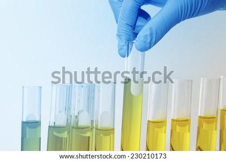 Chemist holding sample of liquid in lab or laboratory - stock photo
