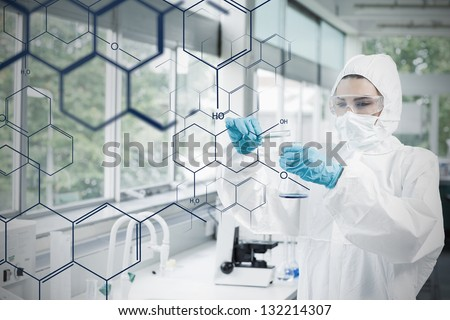 Chemist in protective suit working with futuristic interface with formula diagram on it - stock photo