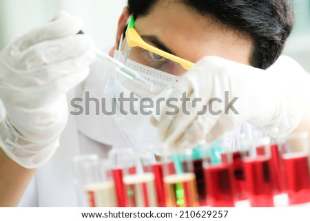 Chemist is analyzing sample in laboratory room. - stock photo