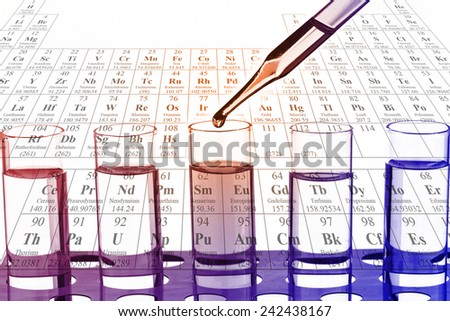 Chemist is dropping the clear reagent into test tube for testing in laboratory. - stock photo