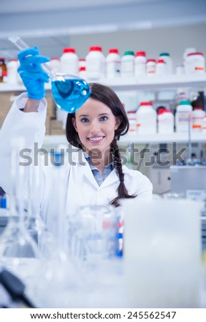 Chemist raising beaker of blue liquid in lab - stock photo