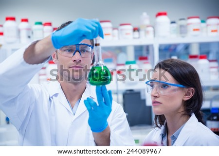 Chemist team looking beaker of green chemical in the laboratory - stock photo